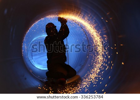 A worker works inside a pipe on a pipeline construction - stock photo