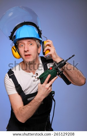 A working man in overalls, helmet and headset, with a drill in his hands is surprised that someone talks to him. He removes his headset in order to hear better.