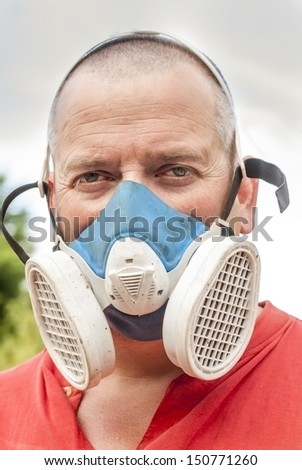 A working man wearing a dust mask - stock photo