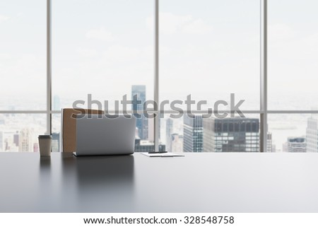 A workplace in a modern panoramic office in Manhattan, New York City. A laptop, notepad and a coffee cup are on the white table. 3D rendering. - stock photo