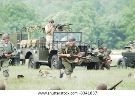 A World War 11 battle reenactment featuring a U.S. Army Jeep and troops.