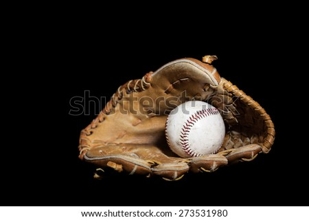 A worn baseball sits inside an old baseball glove on a solid black background.  Image was lit by using a lightpainting technique.