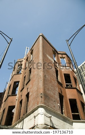 A worn brick building missing windows built in a corner shape. - stock photo