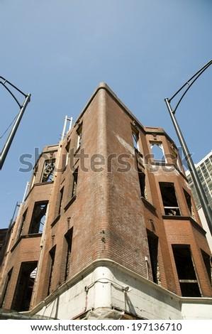A worn brick building missing windows built in a corner shape. - stock photo