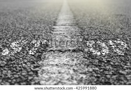 A worn-out stop sign on a tarmac road for the concept: End of the road.  - stock photo