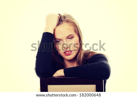 A worried and afraid young woman sitting on chair - stock photo