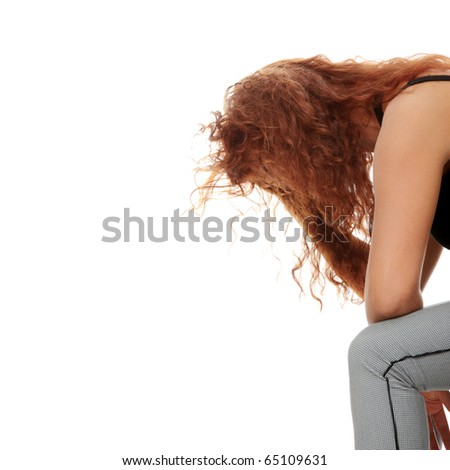 A worried and afraid young woman sitting on chair. Isolated - stock photo