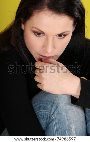 A worried and afraid young woman sitting on the floor.