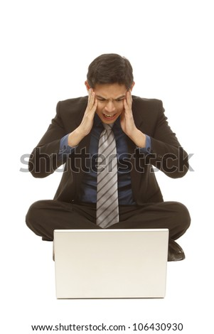 A worried businessman in front of a laptop (isolated on white) - stock photo