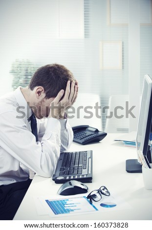 A worried businessman sitting at office desk - stock photo