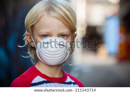 A worried child  wearing a protective face mask to prevent virus infection or pollution.