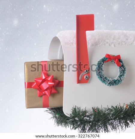 A wrapped Christmas gift sticking out of an open mailbox decorated for the holidays. Square composition with snowy background. - stock photo