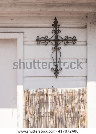 A wrought iron cross hangs on wooden white painted slat walls above some bamboo fencing - stock photo