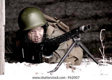 A WW2 american soldier posing with a German MG42 Machine Gun (grainy and sepia tone) - stock photo