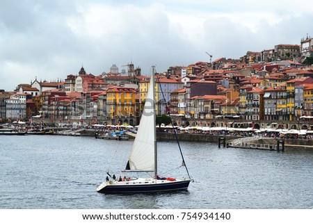 A yacht and the old city of Porto full of tourists