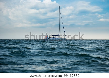 A yacht in a stormy sea. A boat lowered the sails and unrecognisable people - stock photo