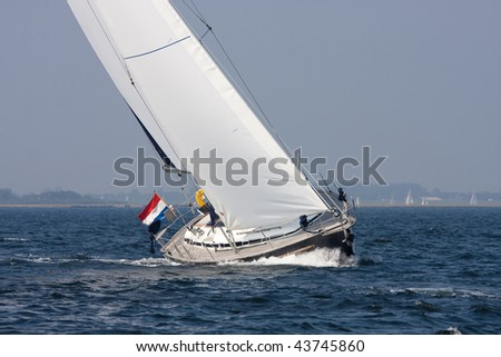 A yacht is cruising in a moderate breeze in lake Grevelingen, Netherlands - stock photo