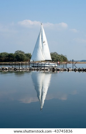 A yacht is reflected in the calm water on a lazy summer day. - stock photo