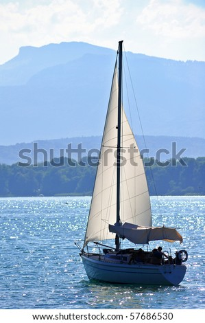 A yacht sailing out into a lake, backlit. Space for text in the sky.
