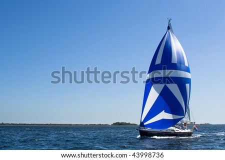 A yacht sails on lake Grevelingen (Netherlands) with a huge blue-white spinnaker on a bright summer day - stock photo