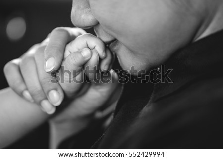 A year old Asian baby holding hand with his mother while breastfeeding