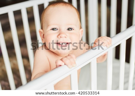 A year old baby is smiling in the crib and holds onto the side of the bed - stock photo