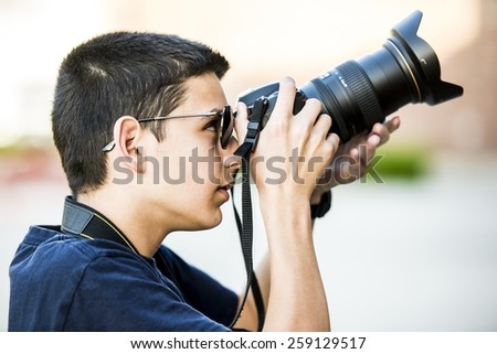 A 12 year old boy about to take a  photograph.
