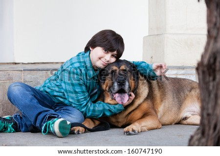A 10 year old boy and his dog sitting down on the sidewalk - stock photo
