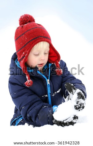 A 3 year old boy child is making bundled up in his winter hat and jacket, making a snowball in the deep white snow. - stock photo