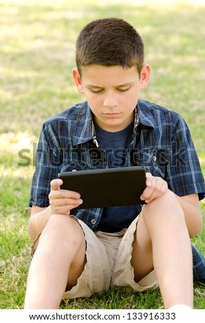a 10 year old boy in the park with his tablet.