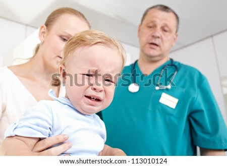 A 1,5 year-old boy is frightened and crying in a medical study. The doctor and the baby'Â?Â?s mother are at a loss. Shallow dof. Focus is on the boy. - stock photo