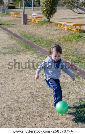 A 2 year old boy kicking a ball in a park. - stock photo