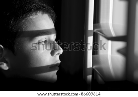 a 9 year old boy looking through the shutters in the early morning.