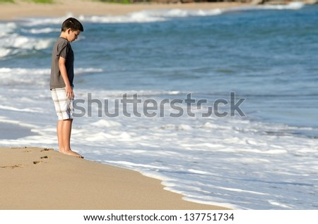a 10 year old boy looks at the waves on the shore of D.T. Flemming Beach on the Island of Maui.