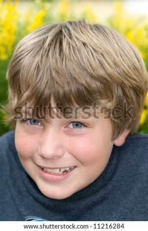 A 9 year old boy smiles while resting in a field of yellow springtime flowers