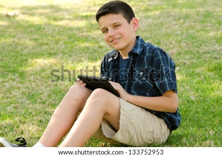 A 10 year old boy smiling while he sits with a tablet  at the park.