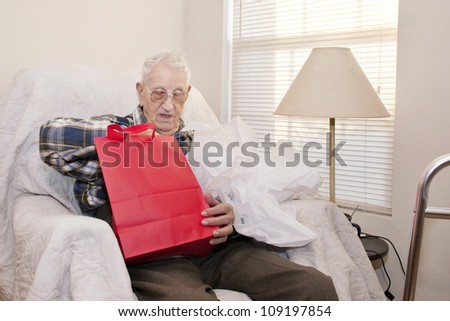 A 94 year old elderly man, sitting alone in his apartment, opening a gift