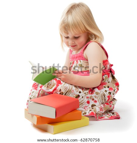 A 4 year old girl in a red dress reads a book.  A pile of books sits next to her.  All of the books have been covered with coloured paper to anonomise them.