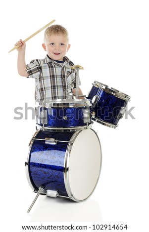 A 2-year-old happily playing a set of shiny blue drums.  On a white background. - stock photo