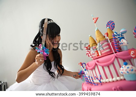 A 15 year old hispanic girl celebrates her birthday with a fancy birthday cake with a candyland theme. The three layer cake is covered with fondant and candy decorations. - stock photo