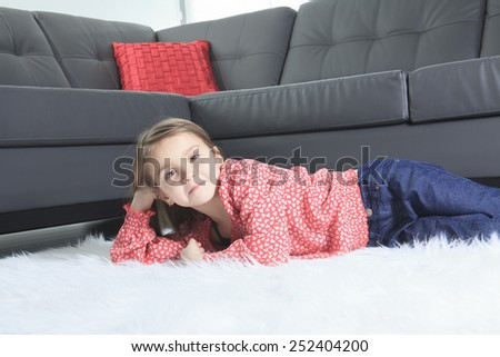 A 8 years old child laying down at home alone - stock photo