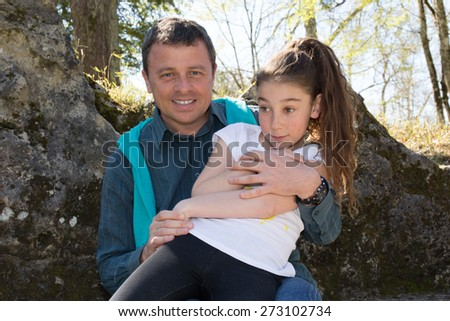 A 10 years old girl enjoying a moment of fun with her dad - stock photo