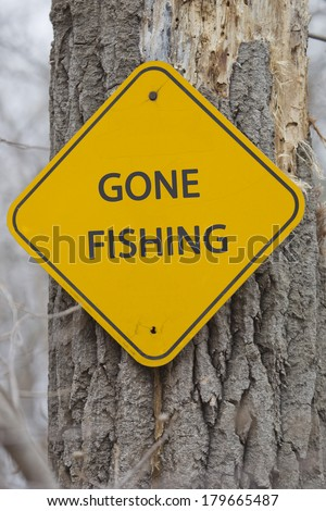 A yellow and black diamond shaped road sign on a tree with the words FREE FISHING DAY making a great concept.