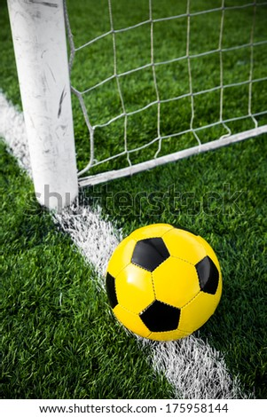 a yellow and black soccer ball in the grass - stock photo