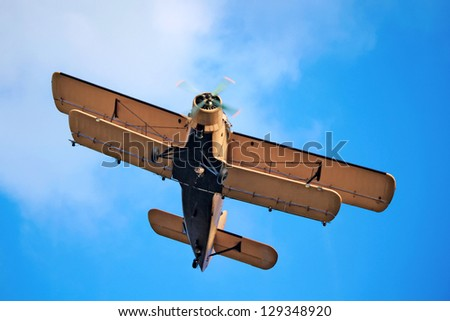 A yellow Antonov AN-2 airplane in front of blue sky, shot from below. This is an agricultural version of the An-2, used mainly for crop-spraying. - stock photo