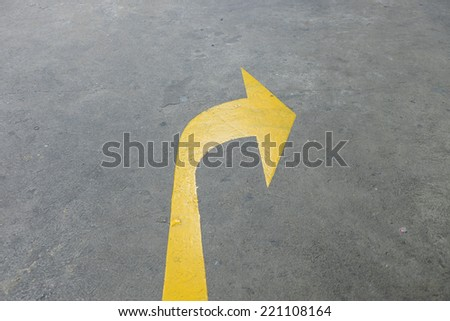 A yellow arrow symbol on a black asphalt road surface. - stock photo
