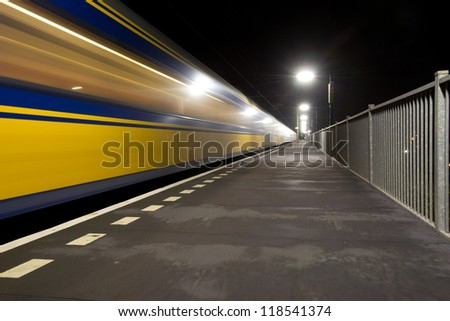 A yellow/blue train arriving at a small train station