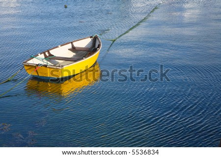 A yellow boat and water ripples.