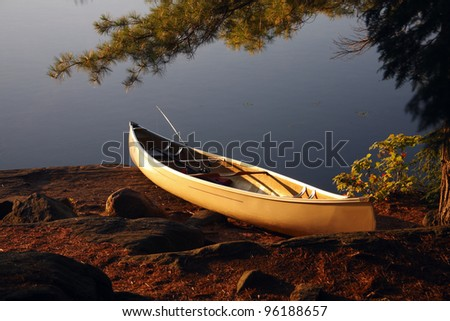 A yellow canoe bathed in sunlight up on the shore at a camp site.