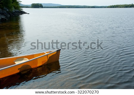 A yellow canoe sits on the shore of Lake Umbagog, on the Maine and New Hampshire border. - stock photo